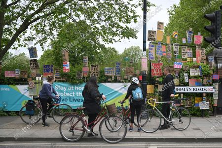 People view signs of support for key workers during the Covid-19 pandemic which are part of an artwork by Peter Liversidge as they are displayed on a road in east London in Britain, 03 May 2020. Countries around the world are taking increased measures to stem the widespread of the SARS-CoV-2 coronavirus which causes the Covid-19 disease.