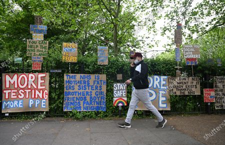 A masked man passes signs of support for key workers during the Covid-19 pandemic which are part of an artwork by Peter Liversidge as they are displayed on a road in east London in Britain, 03 May 2020. Countries around the world are taking increased measures to stem the widespread of the SARS-CoV-2 coronavirus which causes the Covid-19 disease.
