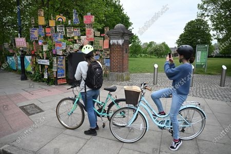 Stock Photo of Cyclists view signs of support for key workers during the Covid-19 pandemic which are part of an artwork by Peter Liversidge as they are displayed on a road in east London in Britain, 03 May 2020. Countries around the world are taking increased measures to stem the widespread of the SARS-CoV-2 coronavirus which causes the Covid-19 disease.