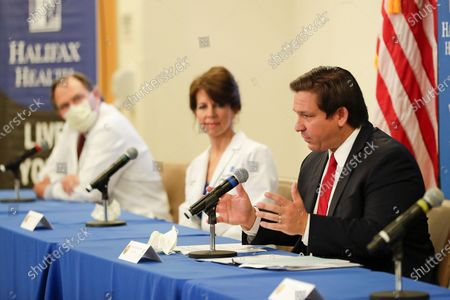 Stock Image of Florida Gov. Ron DeSantis, right, speaks at a news conference at Halifax Health Medical Center about reopening elective surgery in hospitals as Dr. Peter K. Harman, left, and Chief Medical Officer Dr. Margaret G. Crossman, center, listen, in Daytona Beach, Fla. Business owners across much of Florida were busy Sunday preparing to reopen Monday under new restrictions. Gov. Ron DeSantis said he's deliberately taking things slowly during re-opening