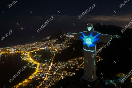 """Rio's Christ the Redeemer statue is lit up as if wearing a protective mask amid the new coronavirus pandemic, in Rio de Janeiro, Brazil, . The message """"Mask saves"""" is written in Portuguese"""