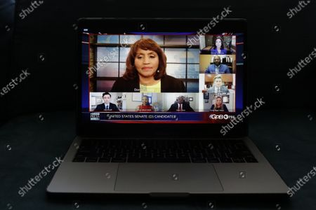 Stock Picture of Donna Lowry, center, and Greg Bluestein, right, third from top, host a virtual debate for Georgia's Democratic for Senate candidates, from bottom left, Jon Ossoff, Maya Dillard Smith, James Knox, Marckeith DeJesus, Sarah Riggs Amico Teresa Tomlinson, seen on a computer screen, in Atlanta. The debate was held in teleconferencing due to the COVID-19 pandemic