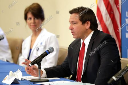 Florida Gov. Ron DeSantis, right, speaks at a news conference at Halifax Health Medical Center about reopening elective surgery in hospitals as Chief Medical Officer Dr. Margaret G. Crossman listens in, in Daytona Beach, Fla