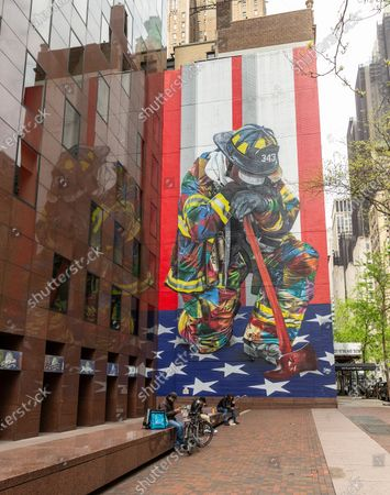 People enjoy warm spring day on Third Avenue with mural Braves of 9/11 by artist Eduardo Kobra amid COVID-19 pandemic