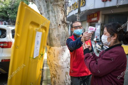 "Stock Picture of Yang Xuebin (L), a member of ""Wuhan Emergency Team"" , measures a resident's body temperature at a community checkpoint in Wuhan, central China's Hubei Province, April 25, 2020.   During the COVID-19 pandemic, Wang Ziyi, Wang Zhen, Li Wenjian, Zhu Wei and Yang Xuebin, the five local residents of the Wuhan city, teamed up to offer free driver service to more than 40 pregnant women without access to vehicles to the hospital. As the impact of the COVID-19 pandemic wanes, the five volunteers have now returned to normal work and social life."