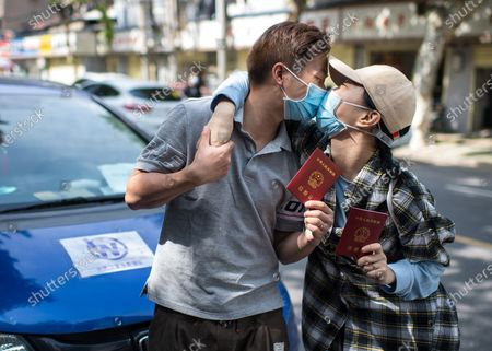 "Wang Zhen (L) and Wang Ziyi, members of ""Wuhan Emergency Team"" , pose for a photo holding their marriage certificates in Wuhan, central China's Hubei Province, April 25, 2020. The couple got married on April 15.   During the COVID-19 pandemic, Wang Ziyi, Wang Zhen, Li Wenjian, Zhu Wei and Yang Xuebin, the five local residents of the Wuhan city, teamed up to offer free driver service to more than 40 pregnant women without access to vehicles to the hospital. As the impact of the COVID-19 pandemic wanes, the five volunteers have now returned to normal work and social life."