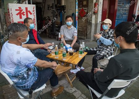 "Members of ""Wuhan Emergency Team"" , Li Wenjian, Yang Xuebin, Wang Zhen, Wang Ziyi and Zhu Wei (from L to R), chat during a get-together in Wuhan, central China's Hubei Province, April 25, 2020.   During the COVID-19 pandemic, Wang Ziyi, Wang Zhen, Li Wenjian, Zhu Wei and Yang Xuebin, the five local residents of the Wuhan city, teamed up to offer free driver service to more than 40 pregnant women without access to vehicles to the hospital. As the impact of the COVID-19 pandemic wanes, the five volunteers have now returned to normal work and social life."