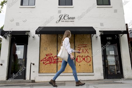 A woman walks past a boarded up J. Crew storefront along 14th Street in Northwest Washington. The parent company of clothing chain J. Crew has filed for Chapter 11 bankruptcy, yet another casualty of the coronavirus pandemic that is wreaking havoc on the retail world. Retail veteran Mickey Drexler led J. Crew for more than a decade, helping it become a coveted fashion brand before it hit a multi-year sales slump
