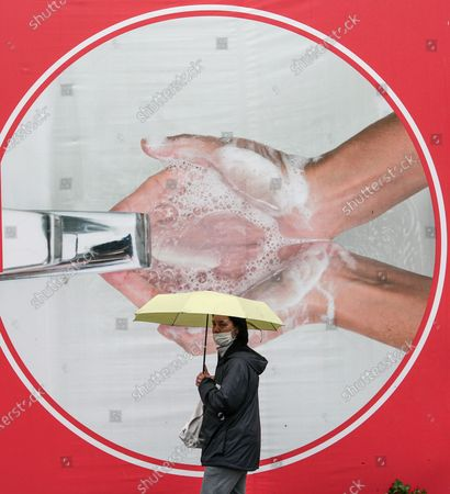 A woman wearing a face mask takes shelter under an umbrella on a rainy day as she  walks in front of advertisement promoting good hand washing practices, in Istanbul, Turkey, 04 May 2020, during the coronavirus disease (COVID-19) pandemic.