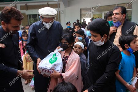 Stock Picture of Former Pakistani cricketer Shahid Afridi, second left, distributes food supplies to people during a government-imposed nationwide lockdown to help contain the spread of the coronavirus, in Quetta, Pakistan
