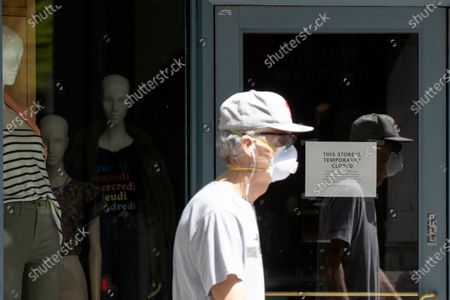 Stock Photo of Person wearing a protective face mask as a precaution against the coronavirus walks past a shuttered J. Crew storefront in Philadelphia, . The parent company of clothing chain J. Crew has filed for Chapter 11 bankruptcy, yet another casualty of the coronavirus pandemic that is wreaking havoc on the retail world. Retail veteran Mickey Drexler led J. Crew for more than a decade, helping it become a coveted fashion brand before it hit a multi-year sales slump