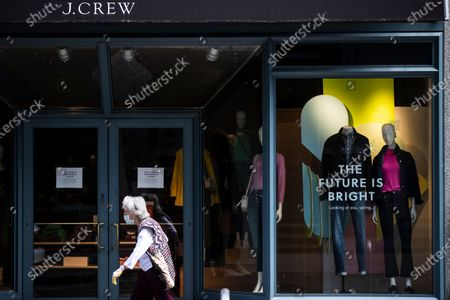 Person wearing a protective face mask as a precaution against the coronavirus walks past a shuttered J. Crew storefront in Philadelphia, . The parent company of clothing chain J. Crew has filed for Chapter 11 bankruptcy, yet another casualty of the coronavirus pandemic that is wreaking havoc on the retail world. Retail veteran Mickey Drexler led J. Crew for more than a decade, helping it become a coveted fashion brand before it hit a multi-year sales slump