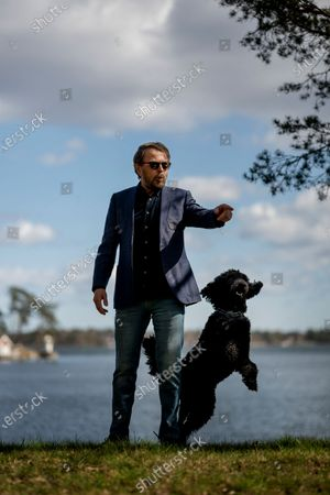 Stock Picture of Björn Ulvaeus and his dog Ares at his house on the private island of Vågaskär, Djursholm outside Stockholm, Sweden