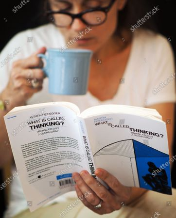 """Exclusive - Professor Kristin Lawler with a book and her morning coffee. She says she is still adjusting to the new normal of 'Zoom' classes, but that """"nothing compares to teaching person to person and with a good old-fashioned textbook."""""""