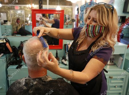 Michelle Harris gives a client a haircut at Rockabetty's Hair Parlor, in Yuba City, Calif., . Monday was the first day businesses could open in Sutter County under a modified public health order