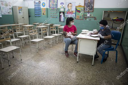 Stock Picture of Teacher Elizabeth Franco, right, corrects the schoolwork of a student brought by his mother to the classroom in Caracas, Venezuela, . Franco goes a few hours every day to the school to correct homework because she does not has a smart phone and internet at her home