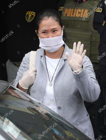 Wearing a mask against the spread of thew new coronavirus, former Peruvian presidential candidate Keiko Fujimori waves reporters as she is released from prison in Lima, Peru, . Fujimori who is the daughter of jailed former president Alberto Fujimori will be released while she is under investigation for money laundering, after Peru's supreme court accepted an appeal and ruled to revoke Fujimori's 15-month jail sentence