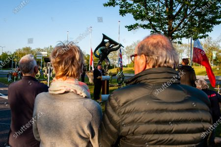 """A group of people is seen gathering during the Mayor's speech. The commemorations took place at the """"Kitty de Wijze"""", a monument that  has become the symbol of the Jewish in Nijmegen who were deported and never come back. This year because of the current situation, the ceremony was held without an audience, just with the presence of Rabbi M. Levin and Mayor of Nijmegen Hubert Brushwood is also the chairman of the Security Council in the country. The memorial service in the Sint Stevens church was canceled this year."""