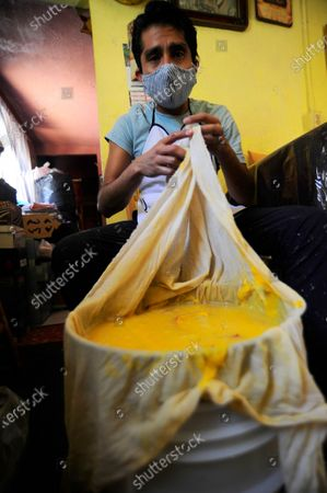 "Stock Image of Carlos Beltran  worker of ""La Paloma Azul""  who has closed  due to the lockdown has been forced to make Pulque at home during the Coronavirus outbreak. Carlos Beltran, who has been making this pre-Hispanic drink  for more than 12 years, offers home delivery to survive the crisis."