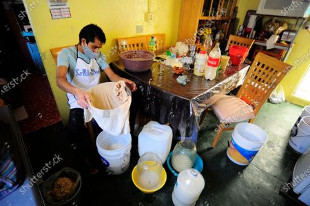 """Stock Image of Carlos Beltran  worker of """"La Paloma Azul""""  who has closed  due to the lockdown has been forced to make Pulque at home during the Coronavirus outbreak. Carlos Beltran, who has been making this pre-Hispanic drink  for more than 12 years, offers home delivery to survive the crisis."""