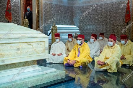 In this photo provided by the Moroccan Royal Palace, Moroccan King Mohammed VI, center flanked by his brother Prince Moulay Rachid, right, and the Crown Prince Moulay Hassan, left, wear face masks as they meditate on the grave of the King's grandfather, HM King Mohammed V, at the Mausoleum of King Mohammed V, in Rabat, Morocco