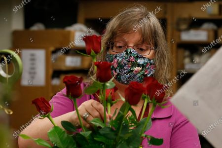 Lisa Phillips arranges a bouquet of roses at Relles Florist in Sacramento, Calif., . Florists are among the retail businesses that Gov. Gavin Newsom said might be eligible to open before the end of this week under upcoming state guidelines concerning the coronavirus
