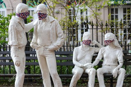 Stock Picture of Protective masks placed on a sculpture by George Segal (1924-2000), created in remembrance of events at the Stonewall Inn and the fight for LGBT rights.