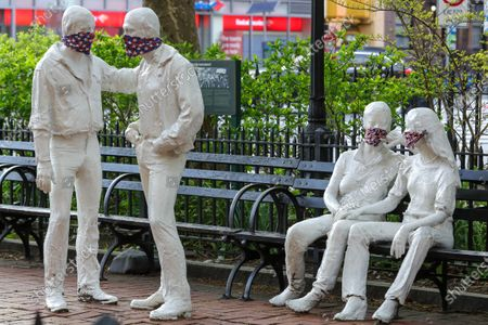 Stock Photo of Protective masks placed on a sculpture by George Segal (1924-2000), created in remembrance of events at the Stonewall Inn and the fight for LGBT rights.