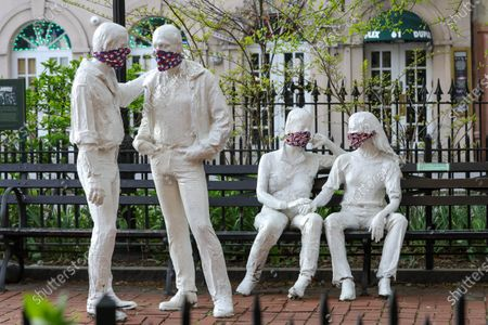 Stock Image of Protective masks placed on a sculpture by George Segal (1924-2000), created in remembrance of events at the Stonewall Inn and the fight for LGBT rights.