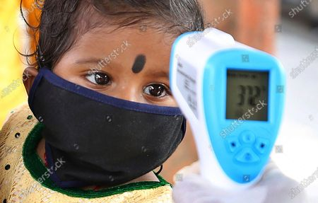An Indian health worker checks the temperature of a child who had been stranded for weeks due to the lockdown to curb the spread of new coronavirus before allowing her to board a bus, in Bangalore, India, . India partly relaxed its lockdown this week