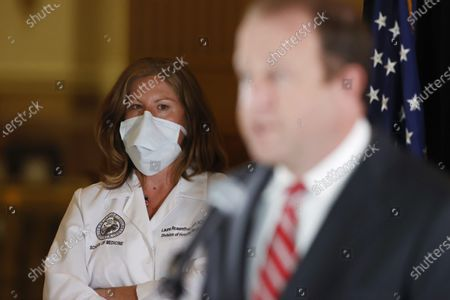 Nurse Lura Rosenthal, back, who is with the University of Colorado School of Medicine, wears a face mask as she listens to Colorado Governor Jared Polis during a news conference to update reporters on the state's efforts to stem the rise of the new coronavirus, in Denver