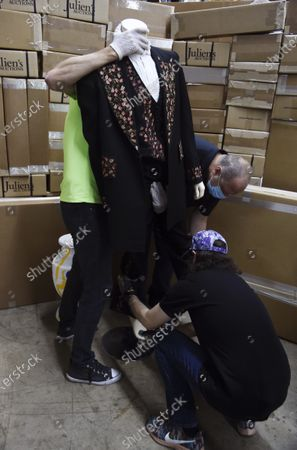 Julian's Auctions workers arrange a suit stage-worn by the late singer Johnny Cash in the 1980s and 1990s, at Julien's Auctions warehouse, in Culver City, Calif. The auction house announced Monday that the suit will be part of a major music artifacts sale taking place on June 19 and 20 in Beverly Hills and online