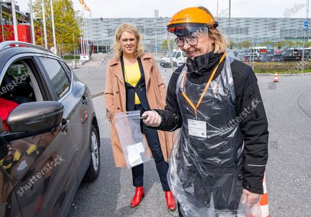 Sweden's Minister for Health and Social Affairs, Lena Hallengren (C) looks on as health worker Gun Bjorling (R) administers a Covid-19 test at a drive-in-test station in Alvsjo. Several Mobile test stations, primarly for health care workers, are set up around Stockhom lately to fight the coronavirus Covid-19 disease.