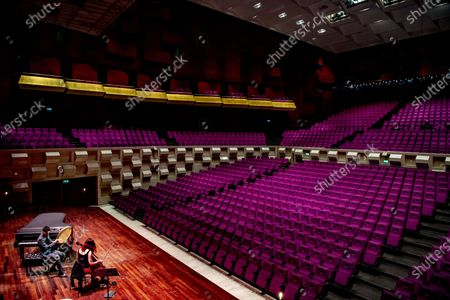Stock Photo of Musicians Farid Sheek and Maya Fridman perform in an empty concert hall De Doelen in Rotterdam, the Netherlands, 07 May 2020. One third of the Dutch theater and concert stages that have missed out on turnover since the coronavirus is in danger of going bankrupt before the  summer.