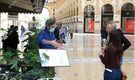Italian chef and television personality Carlo Cracco, wearing a protective face mask, shows the menu of his restaurant  to people in the central Vittorio Emanuele Gallery in Milan, Italy, 7 May 2020. The Italian government is gradually lifting the lockdown restrictions that were implemented to stem the widespread of the Sars-Cov-2 coronavirus causing the COVID-19 disease.