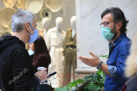 Stock Picture of Italian chef and television personality Carlo Cracco, wearing a protective face mask, shows the menu of his restaurant  to people in the central Vittorio Emanuele Gallery in Milan, Italy, 7 May 2020. The Italian government is gradually lifting the lockdown restrictions that were implemented to stem the widespread of the Sars-Cov-2 coronavirus causing the COVID-19 disease.