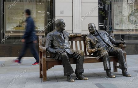 """Pedstrian passes a sculpture by Lawrence Holofcener called """"Allies"""" featuring bronze figures of Winston Churchill and Franklin D Roosevelt, as the country is in lockdown to prevent the spread of coronavirus, in London, . Unlike the mass street celebrations in 1945, surviving veterans are marking V-E Day this year in virus confinement, sharing memories with loved ones, instead of in the company of comrades on public parade"""