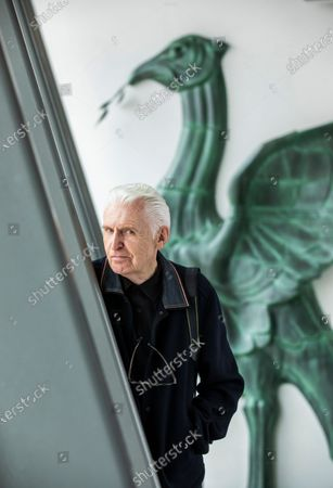 Stock Image of Mike McCartney, 75, brother of Sir Paul McCartney of The Beatles. Mike is a member of the Liverpudlian performance artists The Scaffold, songwriter and photographer but never left his hometown city. Mike is pictured in the Museum of Liverpool which overlooks the famous Liver Building with it's famous Liverbirds which adorn the top turrets. Behind him is a life-size replica of one of the Liverbirds statues.His 1974 album McGear, produced by brother Sir Paul McCartney has been reissued by Esotric.