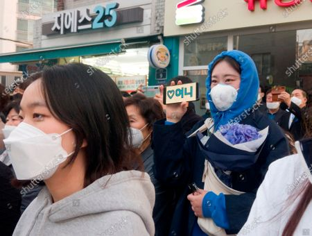 Stock Photo of Supporters of Lee Nak-yeon, Apr 11, 2020 : Wearing masks to prevent COVID-19 coronavirus infection, supporters attend a campaign of Lee Nak-yeon, former prime minister of South Korea and a candidate of the ruling Democratic Party for the April 15 general elections, in Jongno district in Seoul, South Korea. Lee is running for the election in Jongno, a symbolic constituency in Korean politics where influences in politics are elected. Hwang Kyo-ahn, the head of the conservative right wing main opposition United Future Party (UFP), is also running in the constituency. Lee and Hwang have been ranked as the first and second as the next president of South Korea in recent polls. The quadrennial elections will fill the 300-seat unicameral National Assembly of South Korea. Korean characters on a mobile phone (R) read,'Yony', which is short for Lee Nak-yeon.