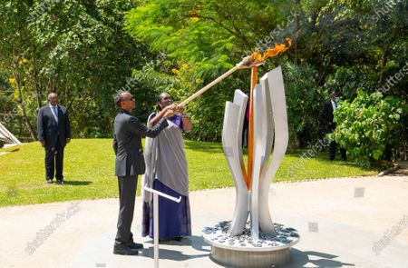 (200409) -- KIGALI, April 9, 2020 (Xinhua) -- Rwandan president Paul Kagame and first lady Jeannette Kagame light a flame of remembrance at the Kigali Genocide Memorial, the final resting place for more than 250,000 victims of the 1994 genocide against the Tutsis, in Kigali, capital city of Rwanda, on April 7, 2020. Rwandans on Tuesday started the commemoration to mark the 26th anniversary of the 1994 genocide against the Tutsis with a low key ceremony at Kigali genocide memorial site as part of preventive measures to contain COVID-19 outbreak in the country.     Rwandan president Paul Kagame and first lady Jeannette Kagame and other dignitaries laid wreaths at the Kigali Genocide Memorial, the final resting place for more than 250,000 victims of the genocide, in the capita city Kigali. (Kigali Genocide Memorial/Handout via Xinhua)