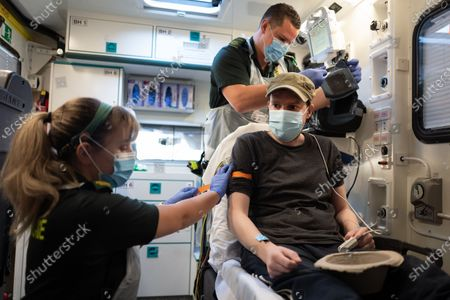 Newly qualified paramedic Nikki Philpott (L) and Paramedic James Hansford treat a patient in the cabin of an ambulance who has previously tested positive for Covid-19 in Portsmouth, Britain, 06 May 2020 (issued 07  May 2020). As the list of recognised Covid-19 symptoms grows, paramedic crews like those with the South Central Ambulance Service are forced to treat every patient as being a potential case, often requiring specialised personal protective equipment (PPE). Paramedics now routinely don what the NHS refers to as Level 2 PPE, like face masks and disposable aprons. Cases with patients potentially needing airway procedures require Level 3 PPE, such as full-face visors and long-sleeved surgical gowns. While the infection rate is falling, and government officials are discussing ways to relax the country's quarantine measures, Covid-19 still creates everyday risks for paramedics and other first responders.
