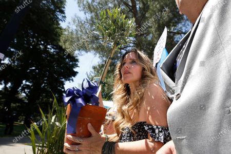 Stock Image of Anti-vaccination activist Tara Thornton tries to a present an olive tree to members of the California Highway Patrol as a peace offering during a demonstration against Gov. Gavin Newsom's stay-at-home order at the Capitol in Sacramento, Calif., . Thornton, who was among the demonstrators arrested by the CHP during a protest last week, was unable to get an officer to accept the tree