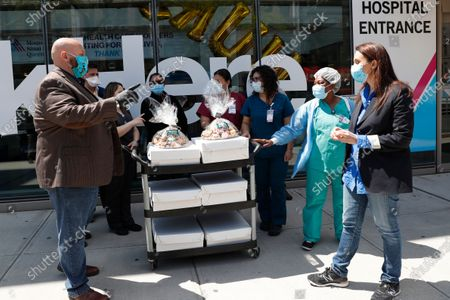 New Yorok State Senate candidate Iggy Terranova, far left, and U.S. congressional candidate Michelle Caruso-Cabrera, far right, chat after donating sandwiches and cookies to emergency room and intensive care unit nurses at Mount Sinai-Queens Hospital during Nurses Appreciation week, in New York. Caruso-Cabrera is opposing U.S. Rep. Alexandria Ocasio-Cortez in New York's 14th congressional district in New York's June 23rd primary election. Caruso-Cabrera says she has been donating lunches since mid-March after connecting via Twitter with an ICU doctor at the hospital and learning what she could do to help