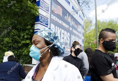 Nurse Neshia McDonald (L) composes herself after discussing a Rikers Island nurse colleague, William Chan, who died yesterday from COVID-19, during a rally organized by the New York State Nurses Association at the entrance to the Rikers Island correctional facility to protest and draw attention to the handling of COVID-19 patients and healthcare worker conditions at the prison in Queens, New York, USA, 07 May 2020. Prisons around the country are seeing large number of COVID-19 cases. New York City is still the epicenter of the coronavirus outbreak in the United States and hospital workers dealing with COVID-19 patients are struggling with a limited supply of protective equipment.
