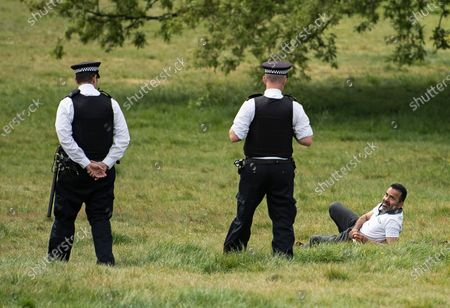 Police officers talk to a man lying down on Primrose Hill in North London, during lockdown. Government is set to announce measures to easy lockdown, which was introduced to fight the spread of the COVID-19 strain of coronavirus..