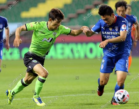 Jeonbuk Hyundai Motors defender Kim Jin-su (L) fights for the ball against Suwon Samsung Bluewings midfielder Kim Min-woo in the opening game of the 2020 K League season at the empty Jeonju World Cup Stadium in Jeonju, South Korea, 08 May 2020. Due to the Coronavirus crisis the 2020 K-League season starts without spectators.