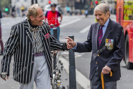 The veteran Mod leaves his scooter to share a joke with Lou Myers, 93, a veteran of the Royal Artillery who comes, from his home in Covent Garden, to pay his respects - he is dissappointed that not many of his comrades came and is frustratedd by the lockdown restrictions ofr older people. He left his wife at home sunbathing on the roof! People gather near the Cenotaph for the 2 minutes silence. VE Day is remembered on its 75th anniversary.