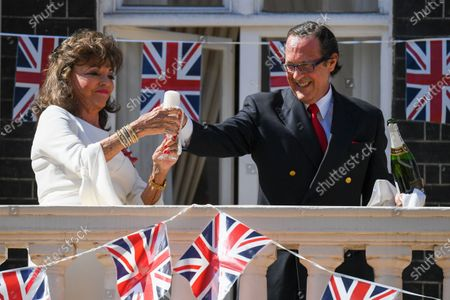 Stock Image of Joan Collins toasts from her balcony with Percy Gibson