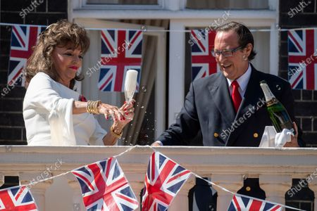 Stock Picture of Joan Collins toasts from her balcony with Percy Gibson