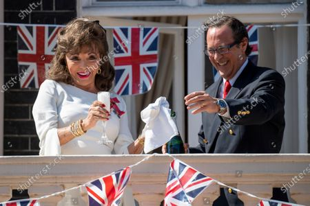 Joan Collins toasts from her balcony with Percy Gibson